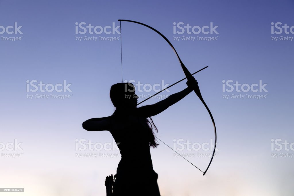 Female ginger hair archer shooting targets with her bow and arrow. Concentration, target, success concept stock photo