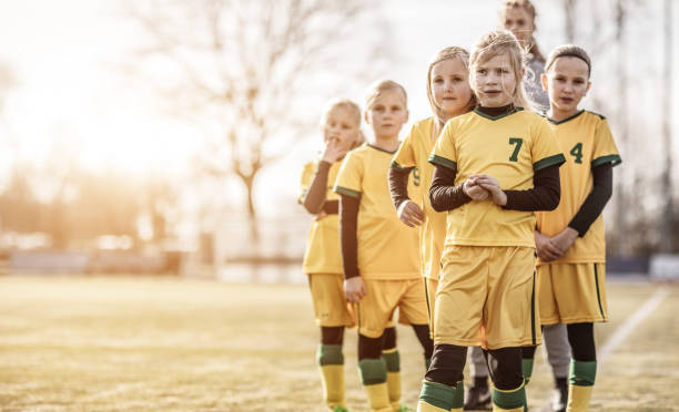 Female Girl Soccer Team running drills at football training with their coaches stock photo