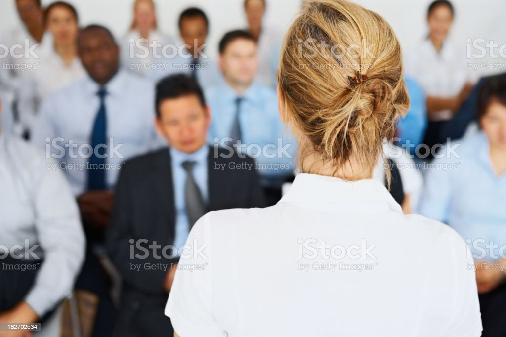 Female giving presentation to her business colleagues stock photo