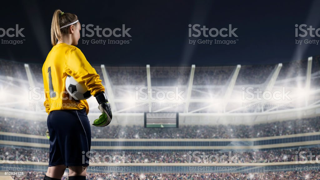 female goalkeeper standing with the ball against the crowded stadium at night stock photo