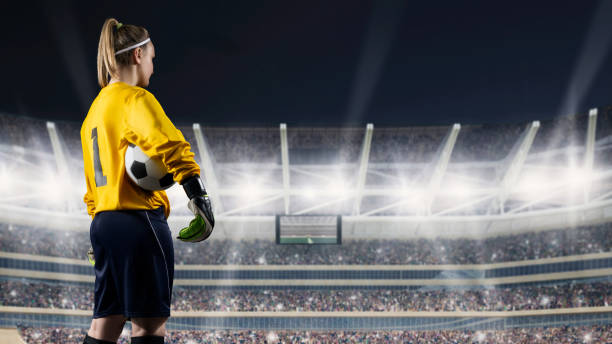 female goalkeeper standing with the ball against the crowded stadium at night - soccer league stock pictures, royalty-free photos & images