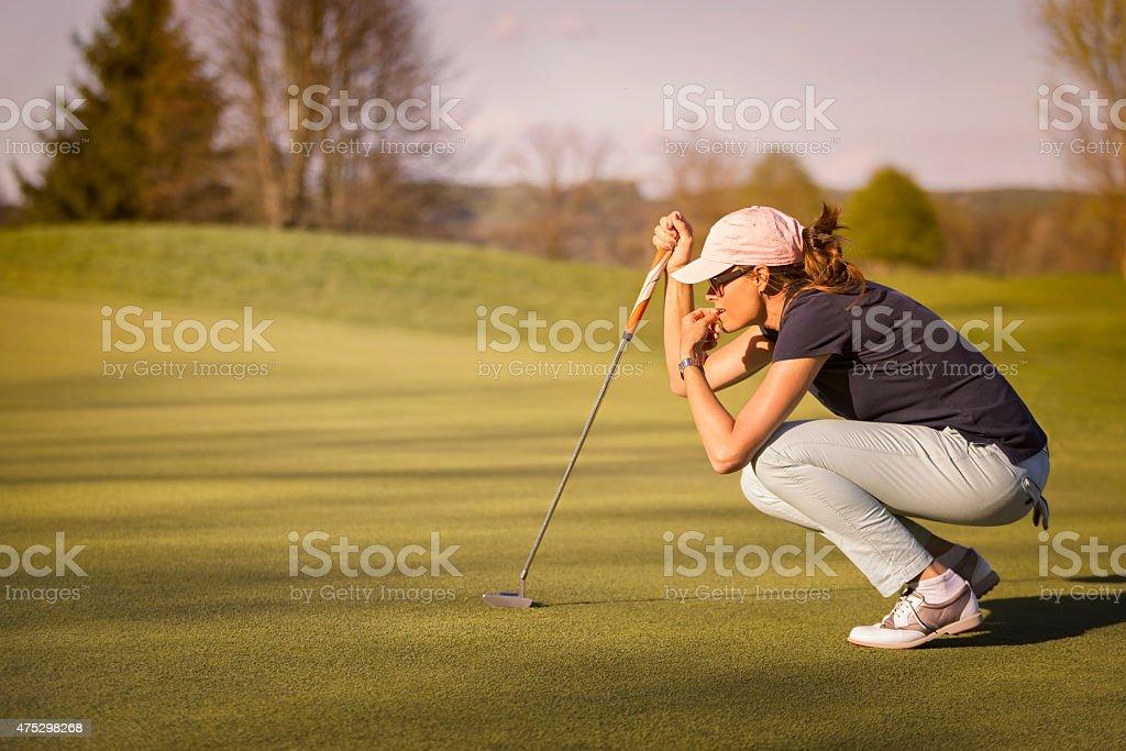 Joueur de golf féminin squats sur le green. - Photo