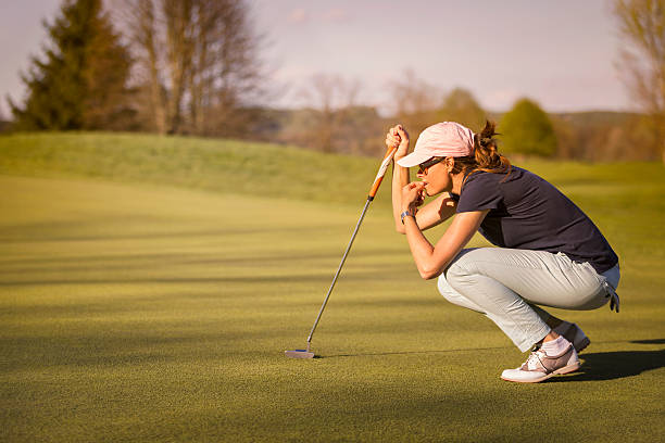 Female golf player squatting on green. stock photo