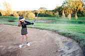 A Female Golfer Escaping a Bunker Shot