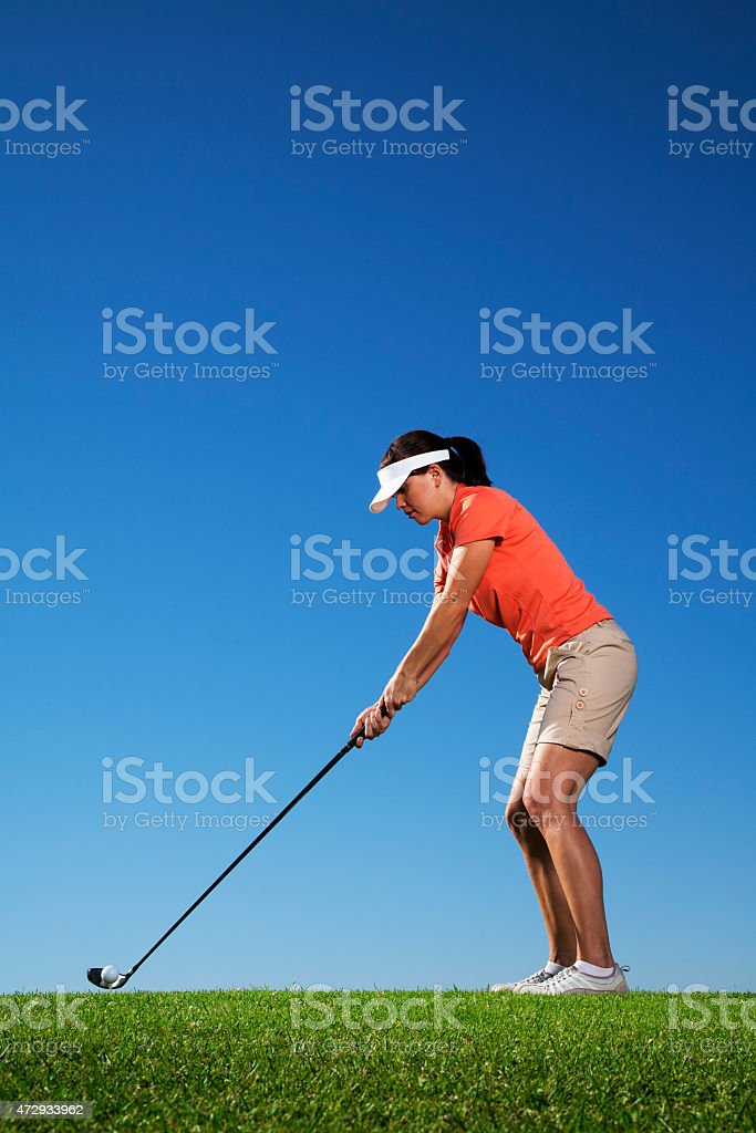 Female Golfer Getting Ready to Tee Off stock photo