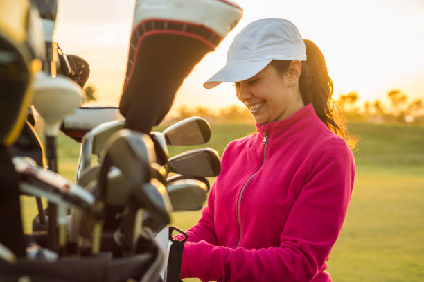 Female Golfer Grabbing clubs out of her golf bag at sunset. stock photo