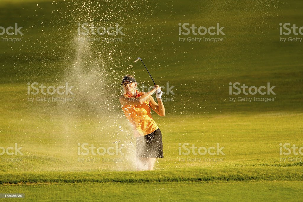 Female Golfer in a bunker stock photo