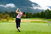 Golfer making the drive. Women in sports. Focus and determination concepts.