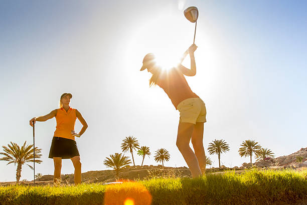 female golfer playing a shot - female golfer stock photos and pictures