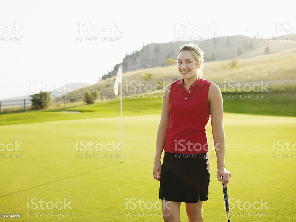 Female golfer standing on green, smiling royalty-free stock photo