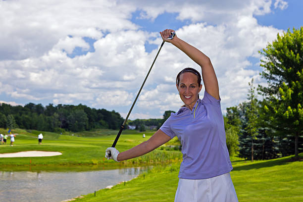 Female golfer stretching with a golf club stock photo