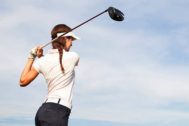 Female golfer swinging golf club behind head stock photo