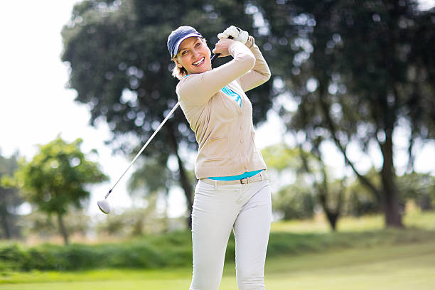 female golfer taking a shot - female golfer stock photos and pictures