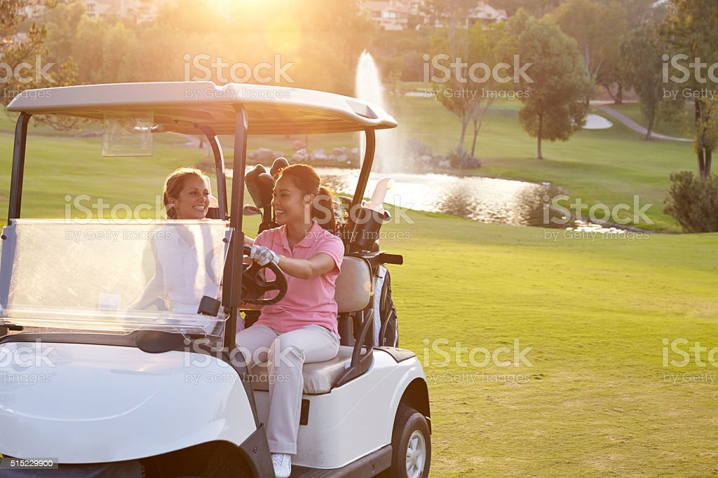 Female Golfers Driving Buggy Along Fairway Of Golf Course stock photo