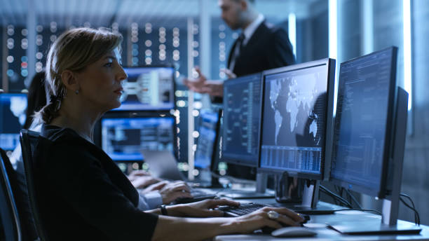 Female Government Employee Works in a Monitoring Room. In The Background Supervisor Holds Briefing. Possibly Government Agency Conducts Investigation. stock photo