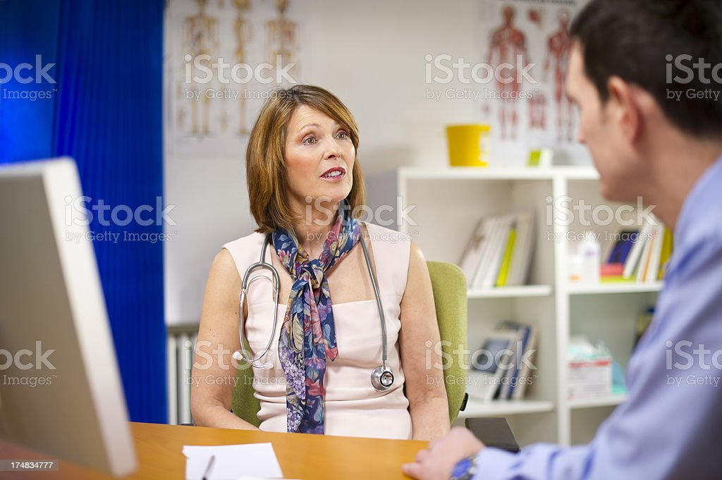 female gp chatting to male colleague or patient royalty-free stock photo