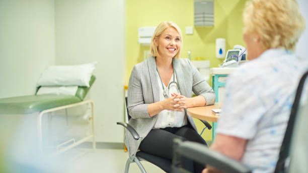 female gp listening to patient a female doc talks to a senior patient in the clinic general practitioner stock pictures, royalty-free photos & images