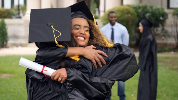 female graduate hugs friend post ceremony - graduation stock pictures, royalty-free photos & images