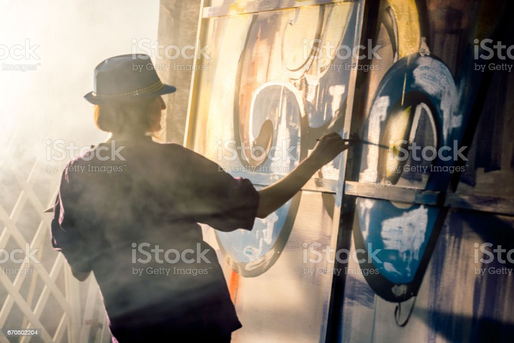 Female Graffiti Artist Is Drawing stock photo