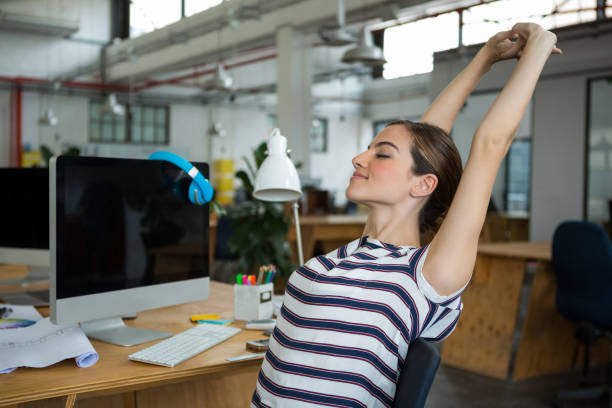 Female graphic designer sitting on chair and stretching her arms stock photo