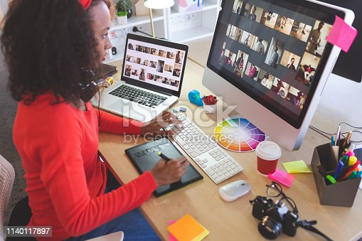 Side view of young mixed-race female graphic designer using graphic tablet at desk in a modern office