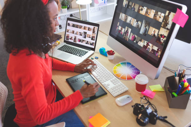 Female graphic designer using graphic tablet at desk stock photo