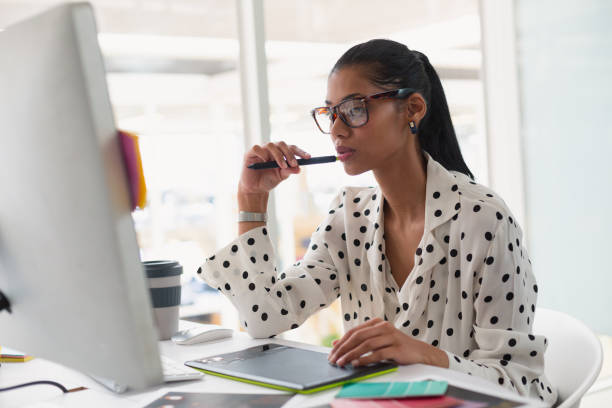Weibliche Grafikdesignerin mit Grafiktablett am Schreibtisch – Foto