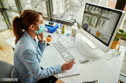 High angle view of businesswoman with face mask analyzing blueprints on desktop PC while working in the office.