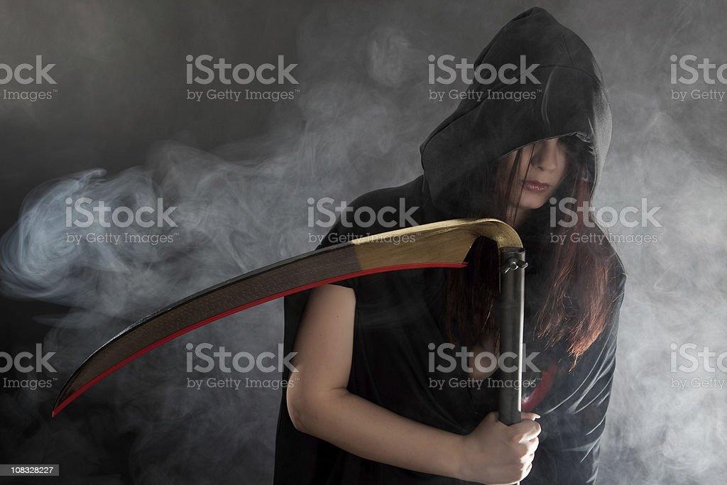 Female Grim Reaper holding a scythe royalty-free stock photo