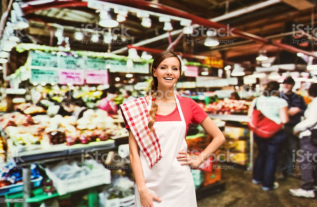 Female grocer in front of market stock photo