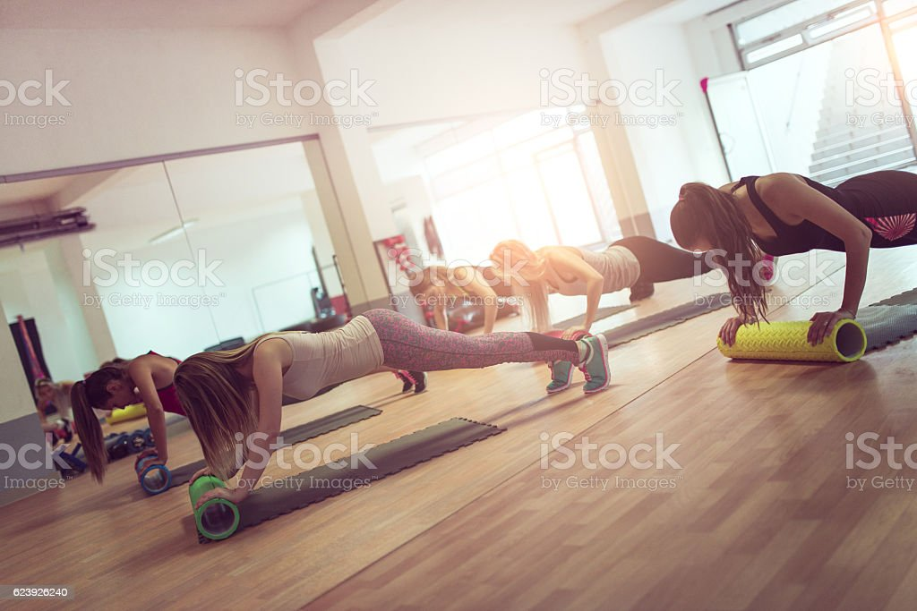 Female Group Exercise in Gym with Cylindrical Rollers on Floor stock photo