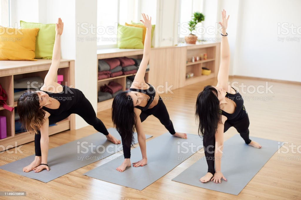 Female Group Of Yogi Practicing In Extended Side Angle Pose