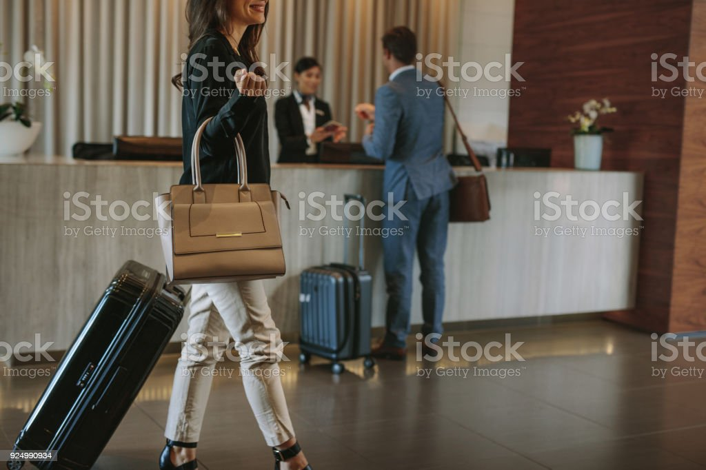 Female guest walks inside a hotel lobby stock photo