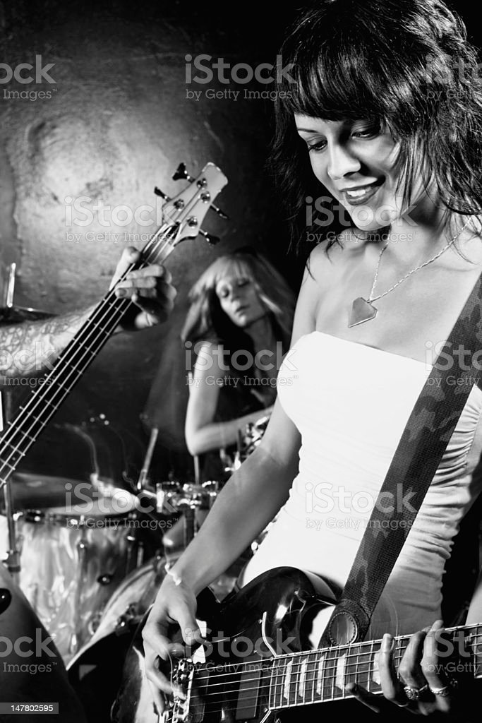 Female guitarist playing in her band stock photo