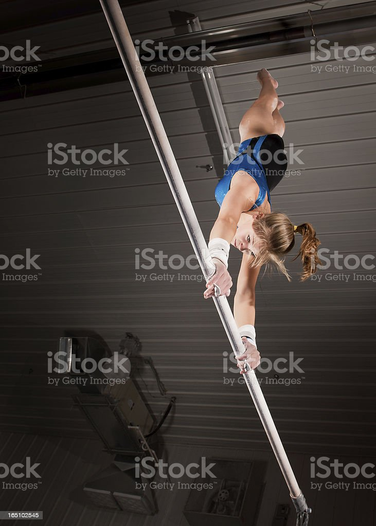 Female gymnast doing handstand on uneven bar in rustic gym stock photo