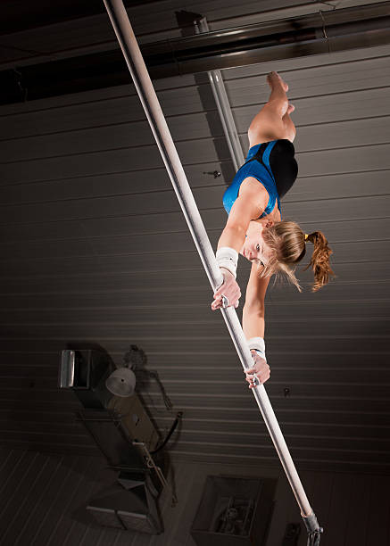 female gymnast doing handstand on uneven bar in rustic gym - uneven parallel bars stock photos and pictures