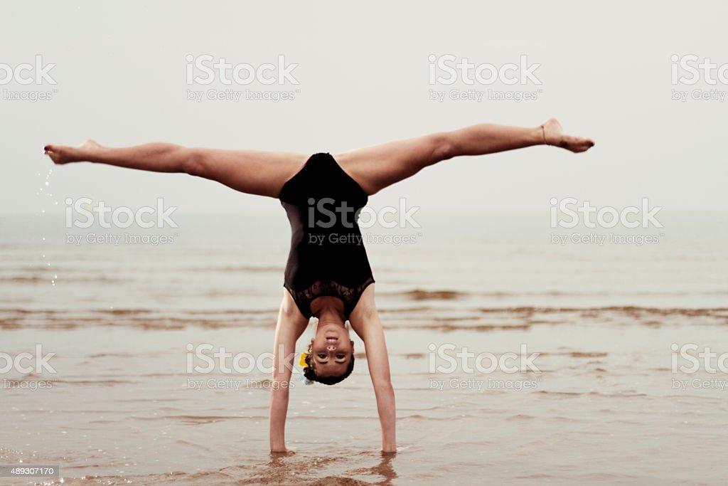 Female gymnast exercising at the seaside stock photo