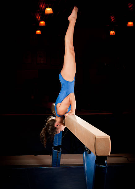 female gymnast in handstand on  balance beam routine - balance beam stock photos and pictures