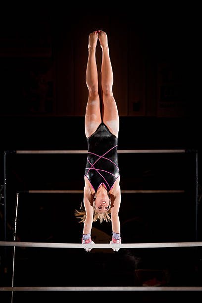 female gymnast in handstand top on uneven bars - uneven parallel bars stock photos and pictures