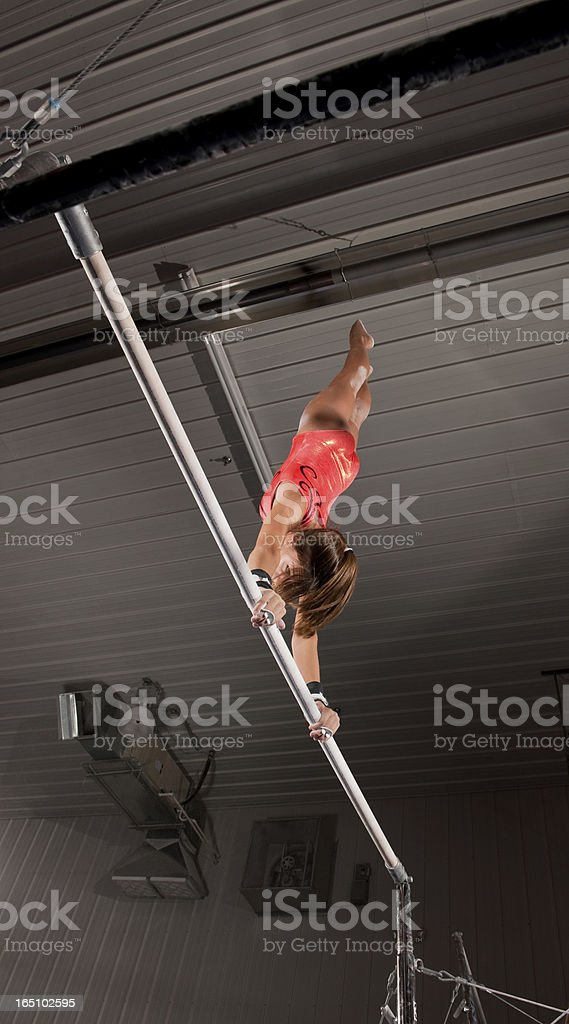 Female Gymnast In Handstand Top On Uneven Bars stock photo