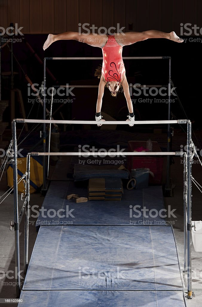 Female Gymnast In Handstand With Straddle On Uneven Bars stock photo