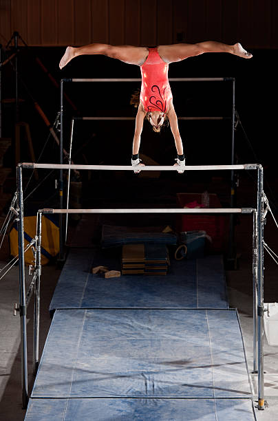 female gymnast in handstand with straddle on uneven bars - uneven parallel bars stock photos and pictures