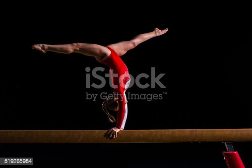 Young woman balancing on balance beam in sports hall.