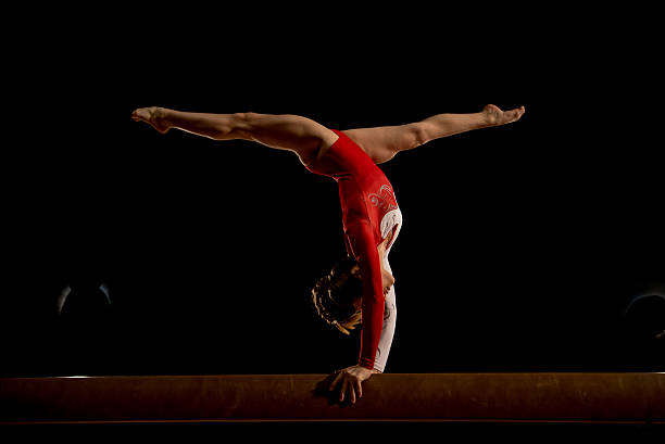 female gymnast in sports hall - balance beam stock photos and pictures
