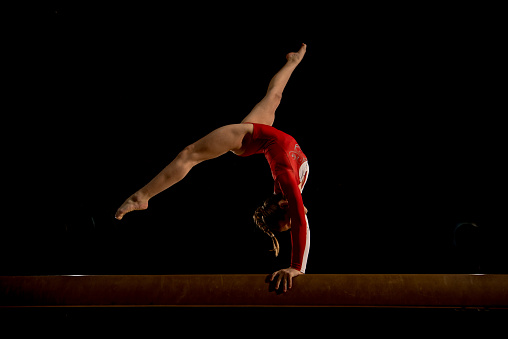 Young woman stretching and balancing on balance beam in sports hall.