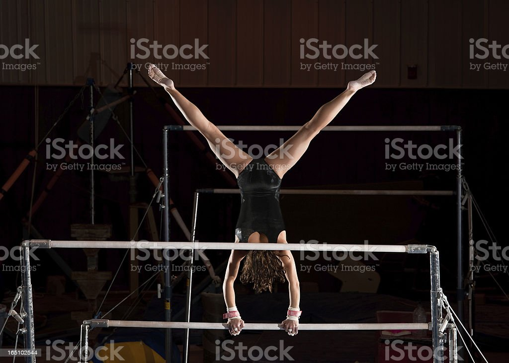 Female Gymnast In Straddle Handstand Top On Uneven Bars stock photo