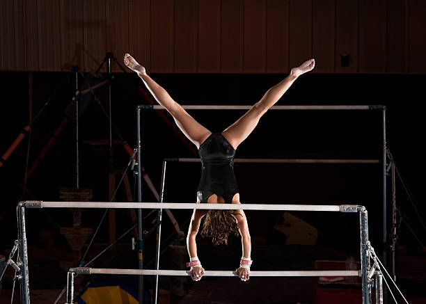 female gymnast in straddle handstand top on uneven bars - uneven parallel bars stock photos and pictures