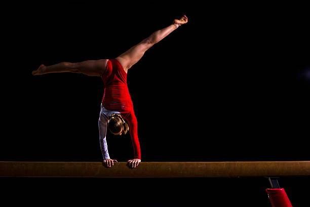 female gymnast on balance beam - balance beam stock photos and pictures