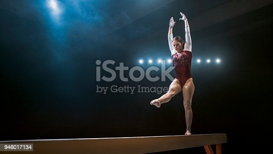 Young female gymnast performing on the balance beam.