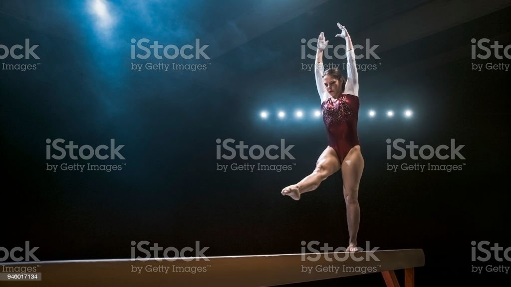 Female gymnast on balance beam stock photo